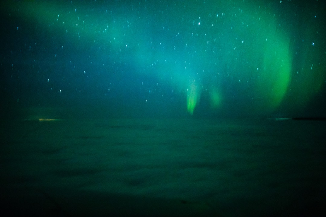 Seeing Northern Lights from a window of a private aurora tour by Wild Nordic in Rovaniemi Lapland Finland.