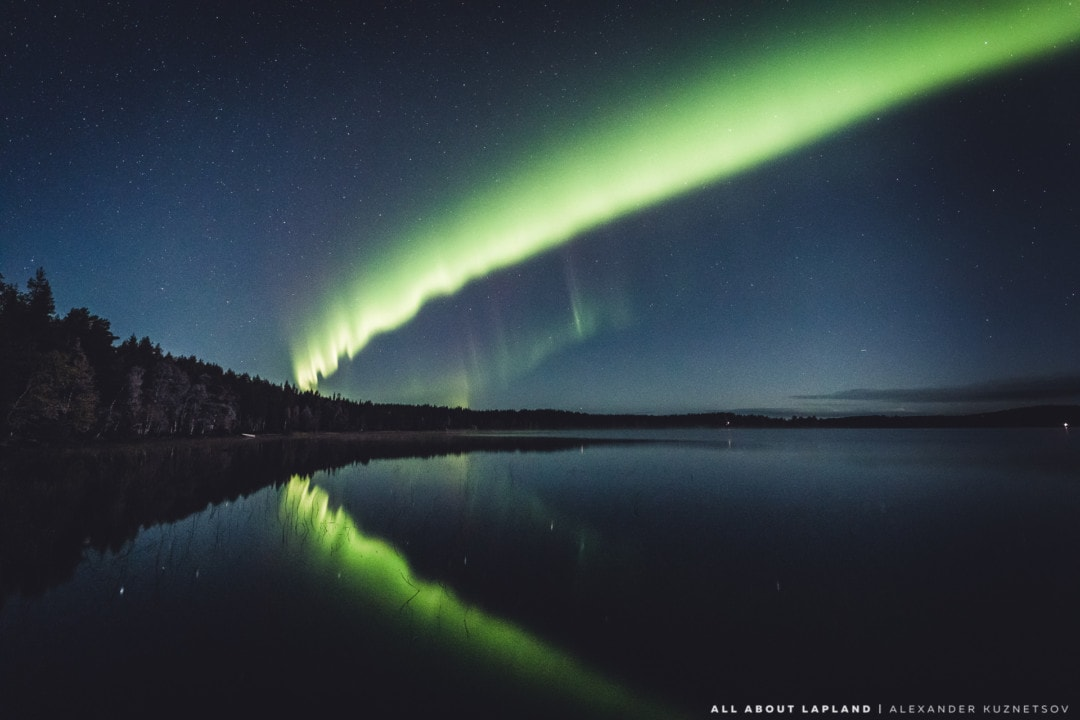 Amazing aurora borealis reflecting in the autumn lake. September in Rovaniemi Lapland Finland.