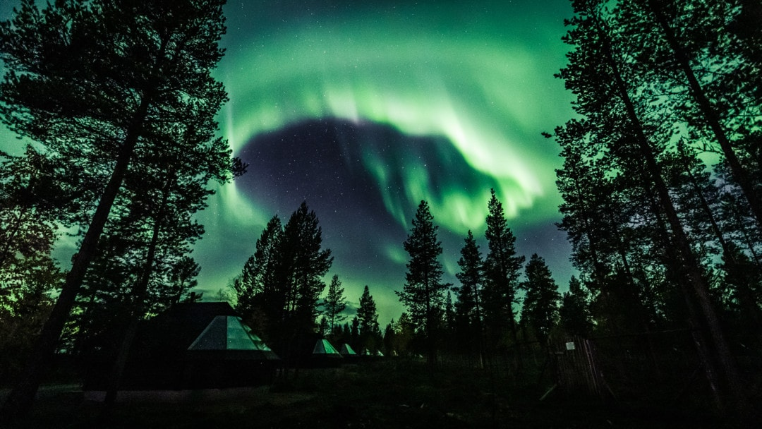 Amazing northern lights over aurora glass igloo cabins in ivalo village Lapland Finland.